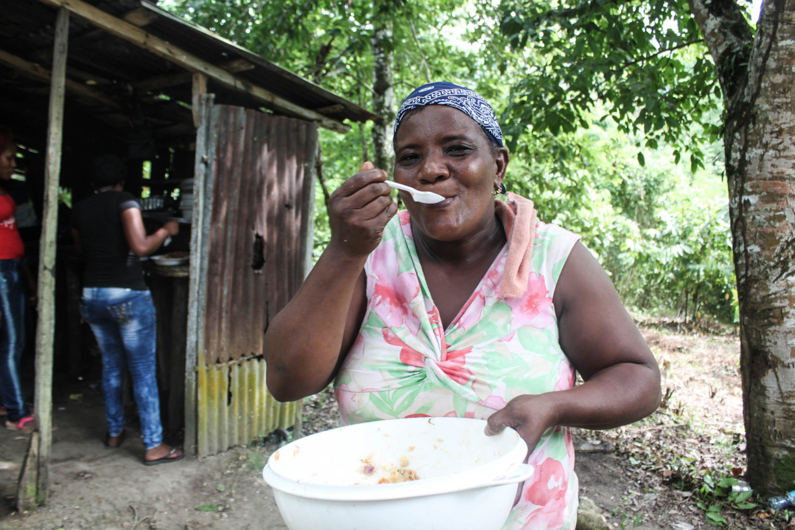 Maria samples some of the food she has prepared for the village.