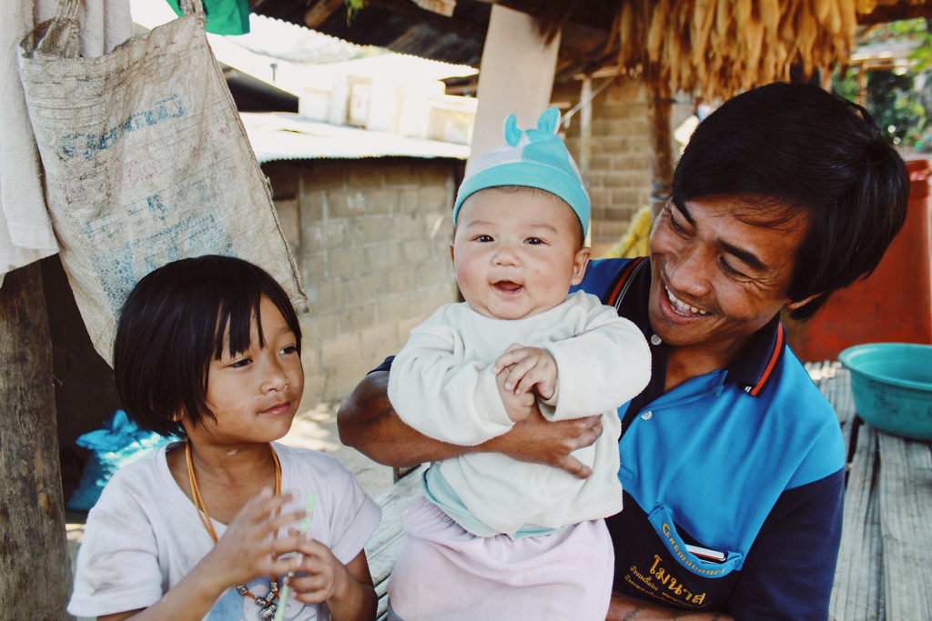 A family's youngest member shares a smile in Thailand.
