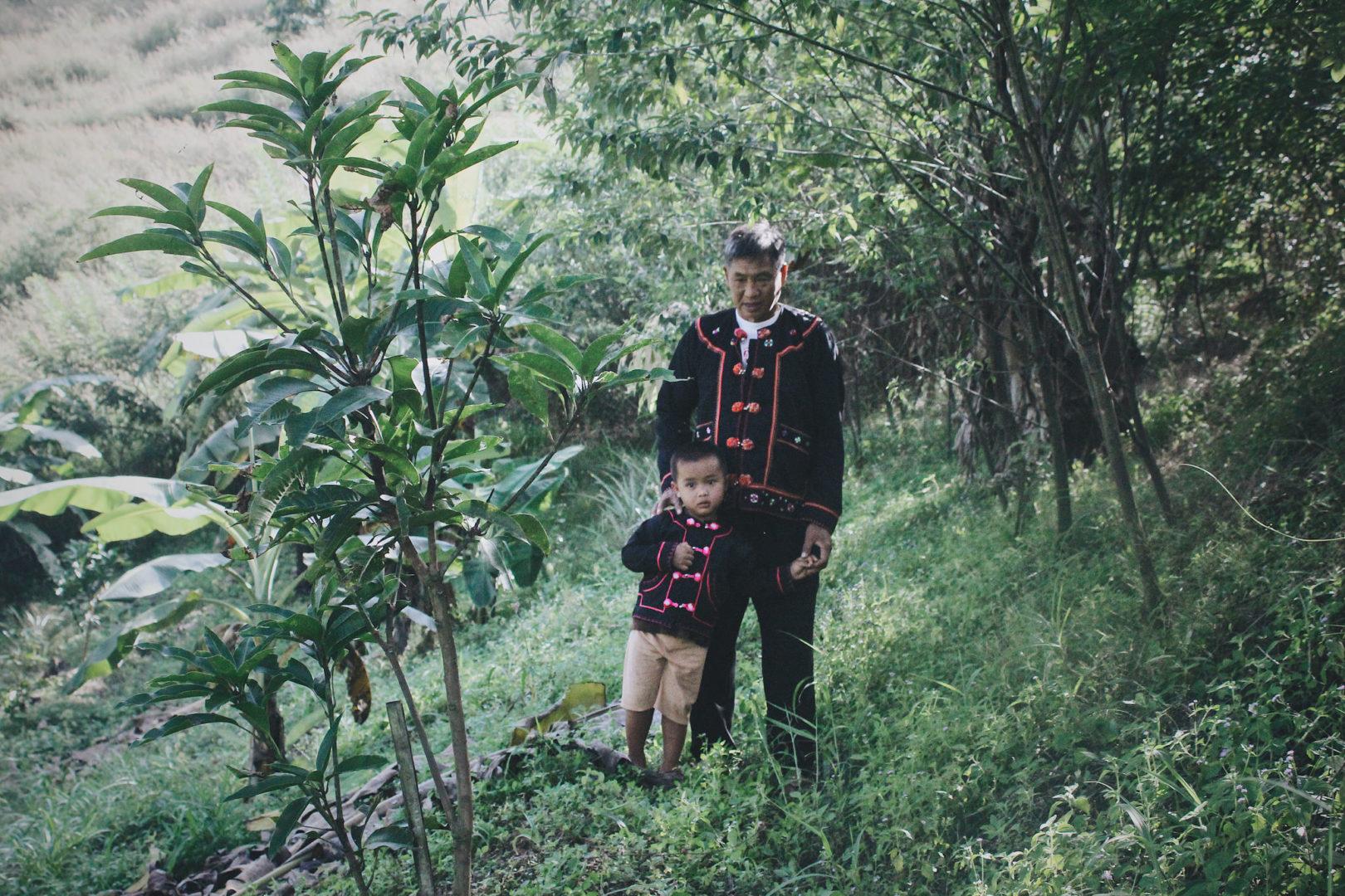 Chagga walks through a farm field with his grandson.