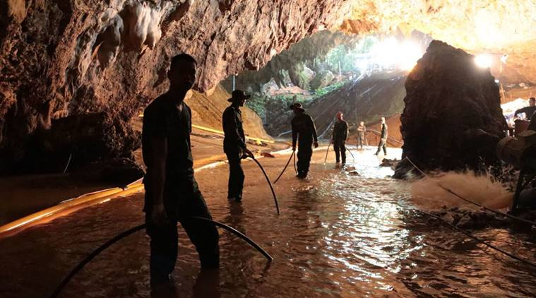 Thai rescue teams arrange water pumping system at the entrance to a flooded cave complex where 12 boys and their soccer coach have been trapped.