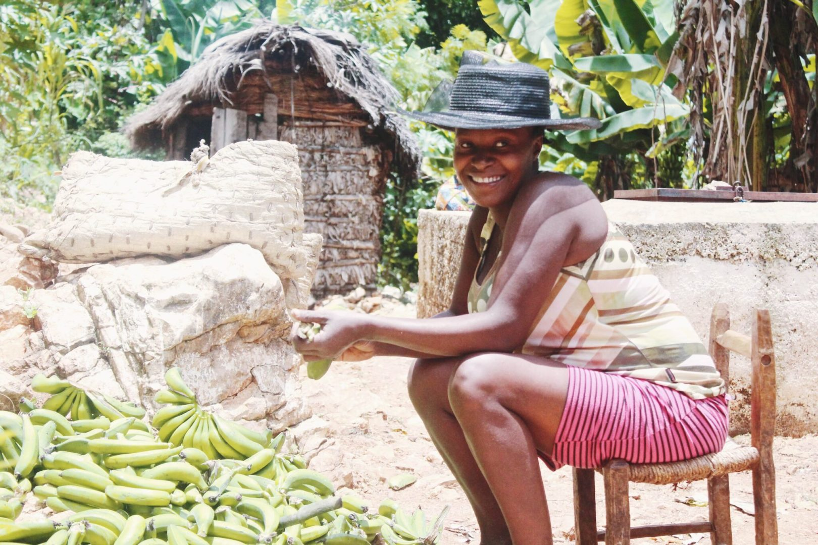 A young woman sorts a banana harvest.